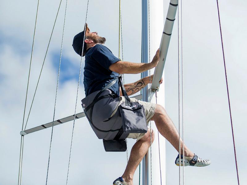Man sitting in Bosun chair climbing mast of sailing vessel