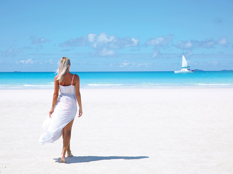 woman in white dress walking on Whitehaven Beach
