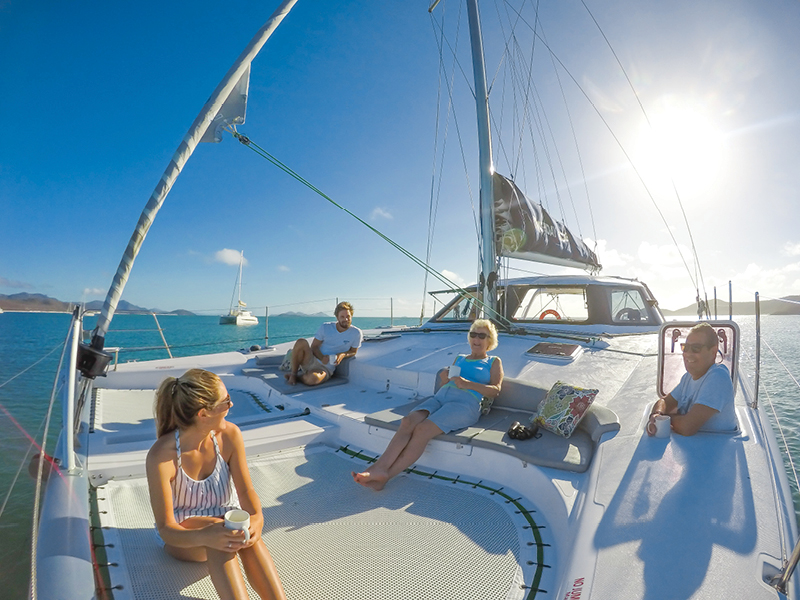 Family relaxing on catamaran in the Whitsunday Islands