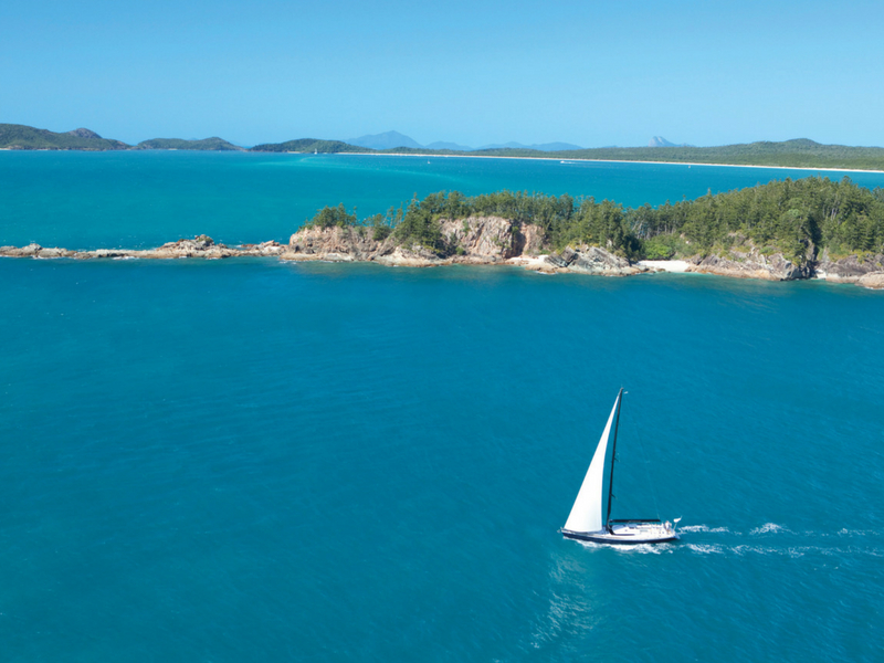 A vessel under sail at Tongue Point near Whitehaven Beach