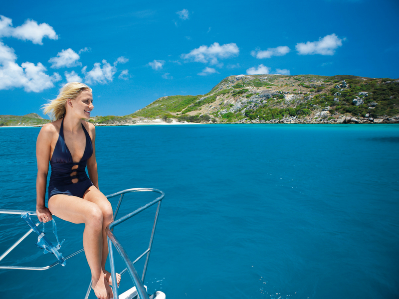A woman on the bow of a vessel at Chalkies Beach in the Whitsundays