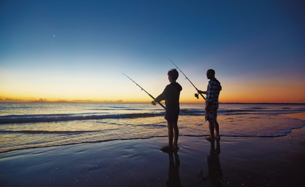 Family fishing at sunset on beach