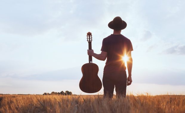 A man holding a guitar in a wheat field at sunset