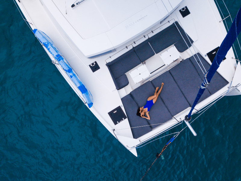 Aerial image of woman relaxing on cushions on the bow of a catamaran with Dream Yacht Charters