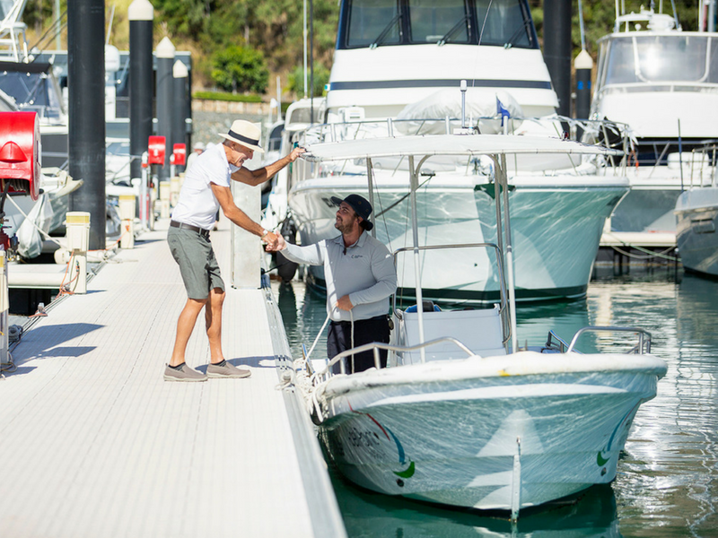 Coral Sea Marina Resort Welcome Vessel tied up and marina concierge welcoming marina guest by shaking hands