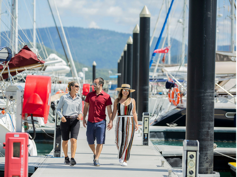 Marina guests walking down dock with Dockhand at Coral Sea Marina