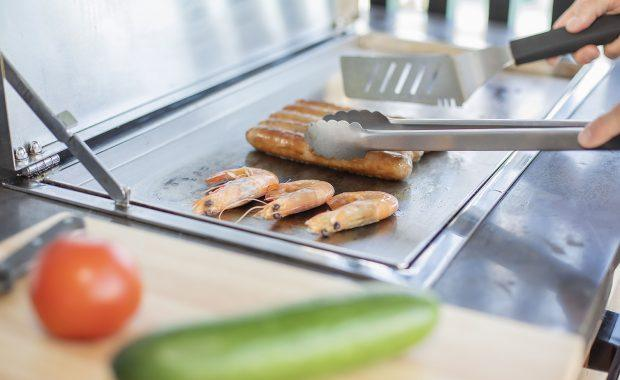 Ocean Club Shipmates Sizzler close up image of a bbq with prawns and sausages