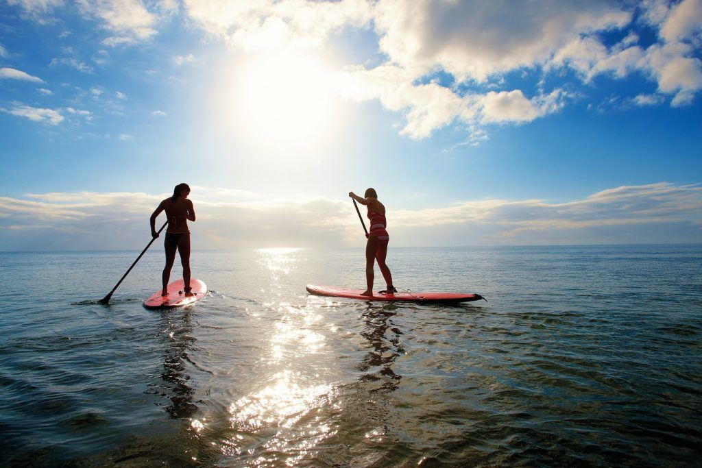 Two women enjoying a Stand Up Paddle Board in the Whitsundays
