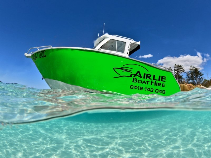 A green vessel from Airlie Boat Hire in the ocean