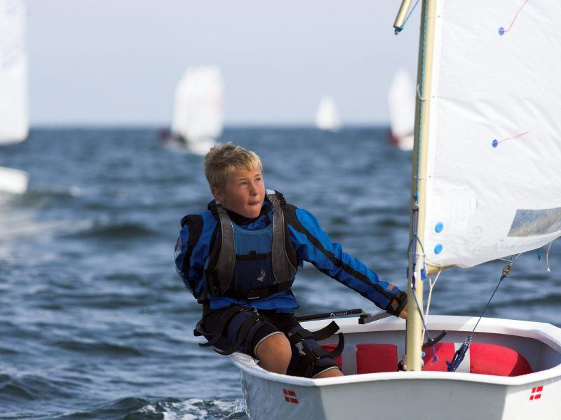 A young boy sailing in a small dinghy