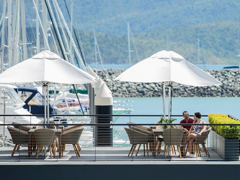 A couple sitting on top of the sun deck at the floating Ocean Club at Coral Sea Marina