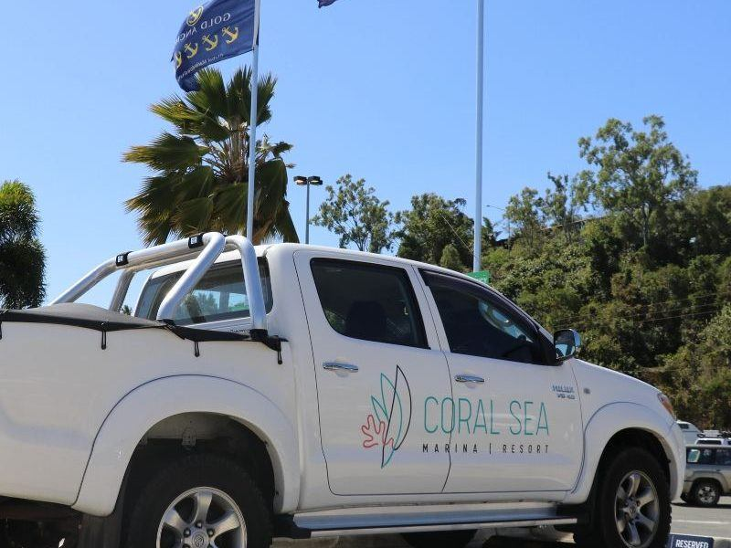 Coral Sea Marina Resort Courtesy Car, a white Toyota Hilux Ute with flags flying in the view