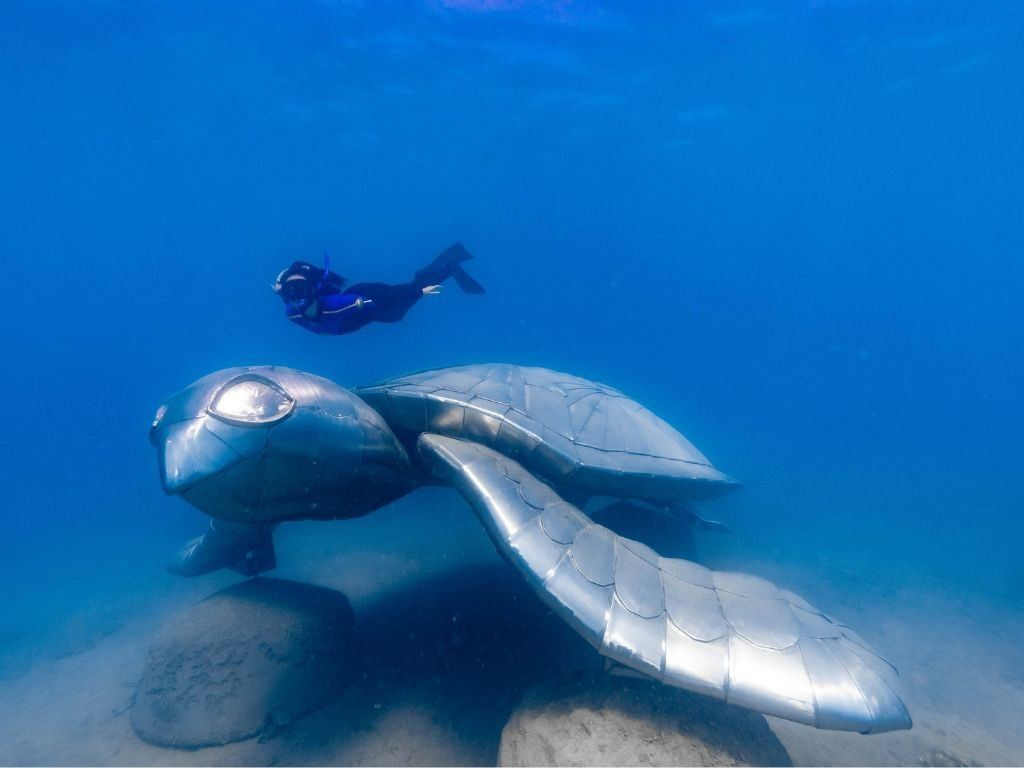 A snorkeler diving next to underwater artwork of a turtle in the Whitsundays