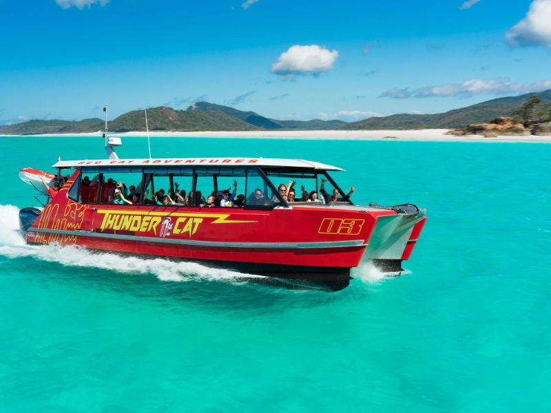 Red Cat Adventures vessel Thundercat driving past Whitehaven Beach on a sunny day with bright blue ocean