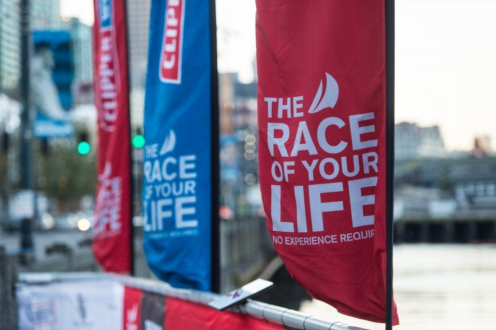 Tear drop flags on the river bank with the Clipper Round the World Yacht Race tagline, 'The Race of your Life'