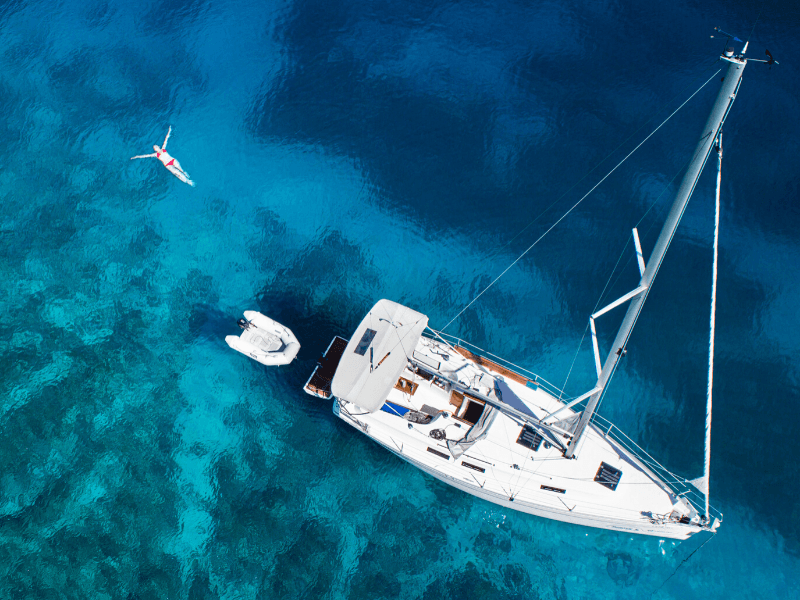 A woman swimming next to her yacht in the ocean