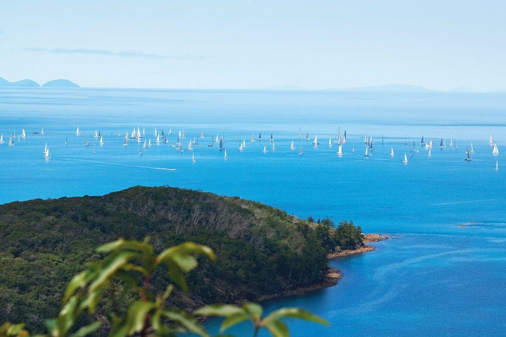 An aerial image of Airlie Beach Race Week showing many boats sailing in the ocean with islands in the distance
