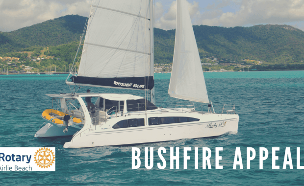 A poster showing a sailing catamaran to advertise the Airlie Beach Rotary Club's Bushfire Appeal