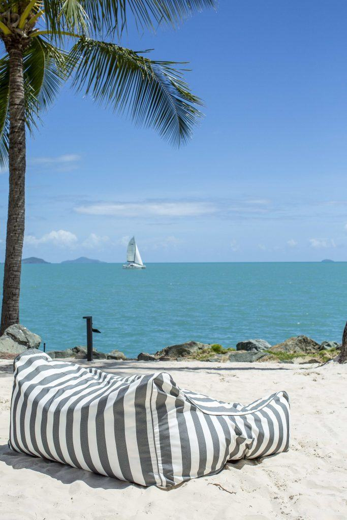 A beanbag on the beach at Coral Sea Resort Hotel facing a view of the ocean with a yacht sailing in the distance