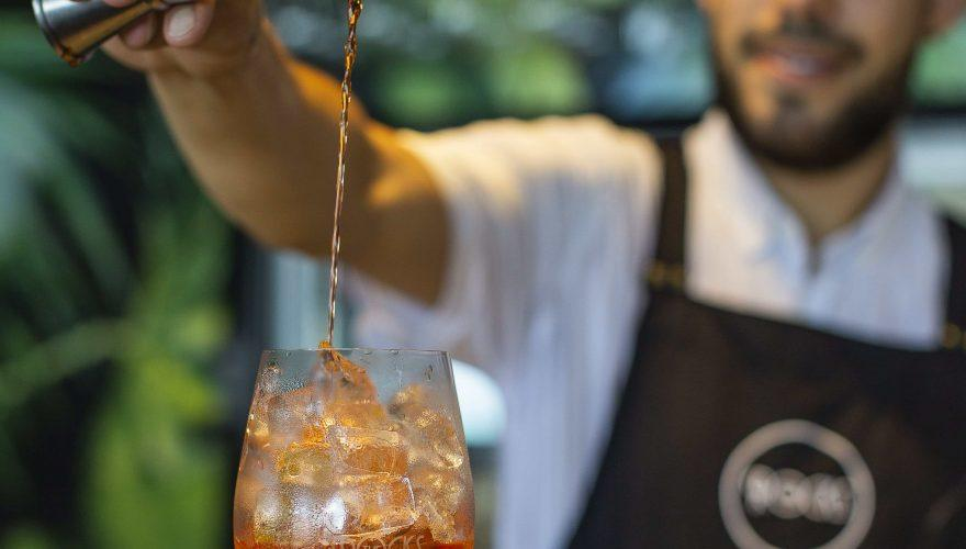 A bar tender at The Rocks - restaurant, bar and pool club, making an Aperol Spritz cocktail
