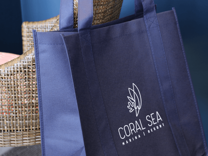 An environmentally friendly reusable shopping bag that has the Coral Sea Marina Resort logo, hanging off the back of a chair