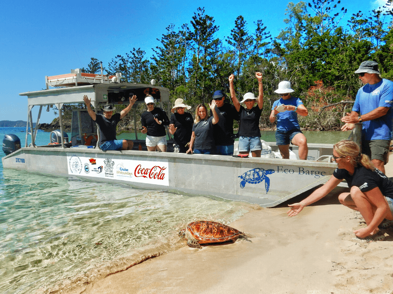 Eco Barge Clean Seas barge with volunteers watching a turtle being released into the ocean