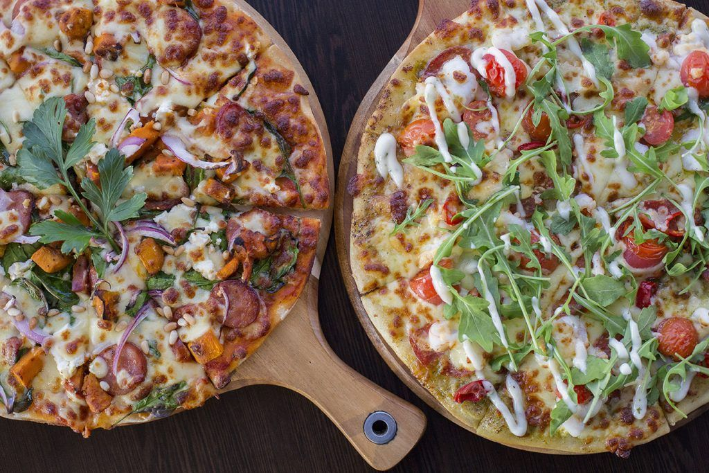 Two pizza's on a wooden board served at Sorrento Restaurant and Bar at Coral Sea Marina Resort