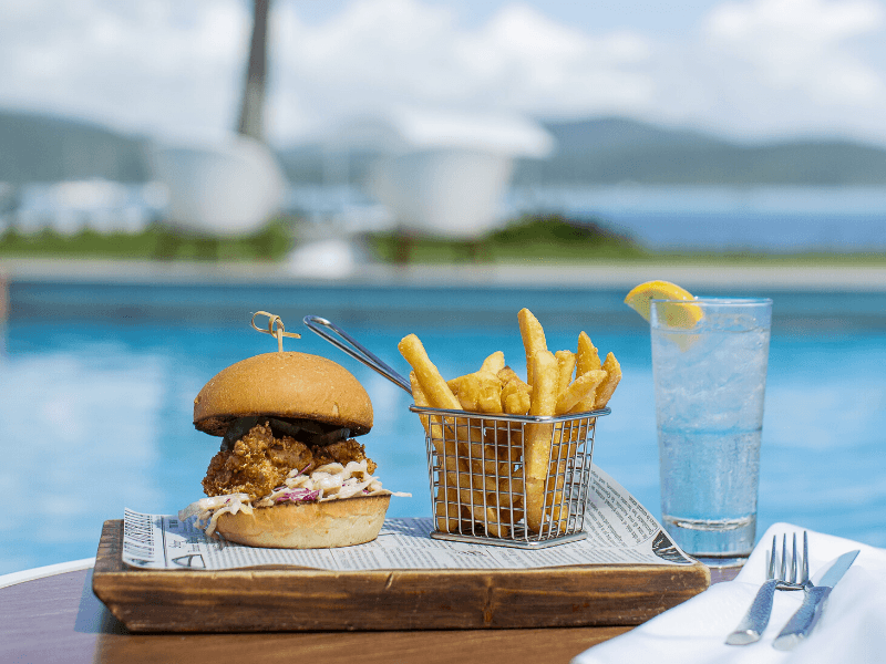 A burger and chips served on wooden board next to the pool at Coral Sea Resort Hotel, at The Rocks
