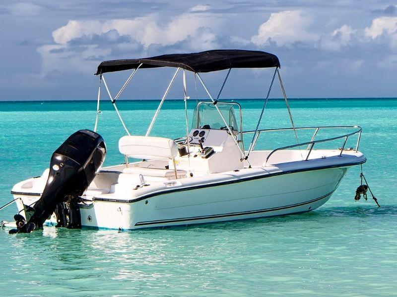 Half Cabin vessel anchored in bright blue water near beach