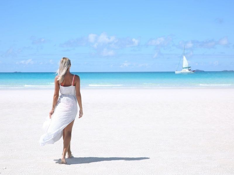 A woman in white dress walking on a the white silica sand of whitehaven Beach in the Whitsundays