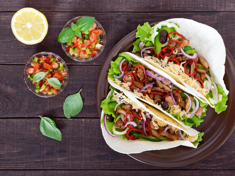 tacos and salsa served on wooden board