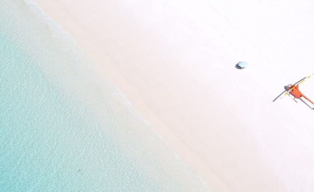 A helicopter at Whitehaven Beach with picnic Umbrella