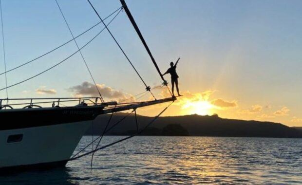 Man standing on the bow of a tallship sailing vessel at sunset