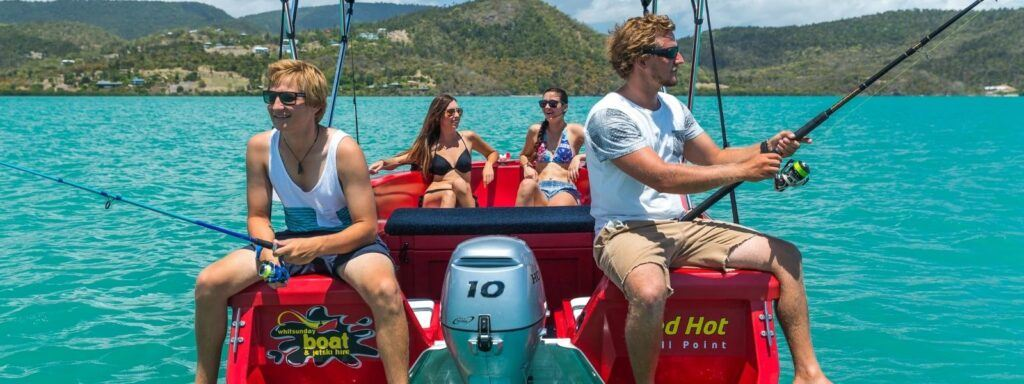 A group of friends fishing and relaxing on a red boat hire tender in the Whitsundays