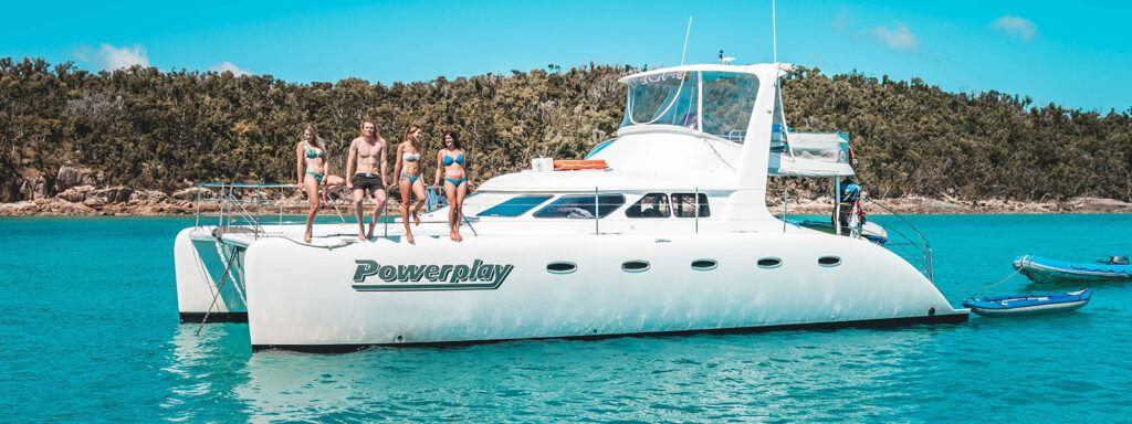 Motor catamaran, Powerplay, anchored in a bay in the Whitsundays
