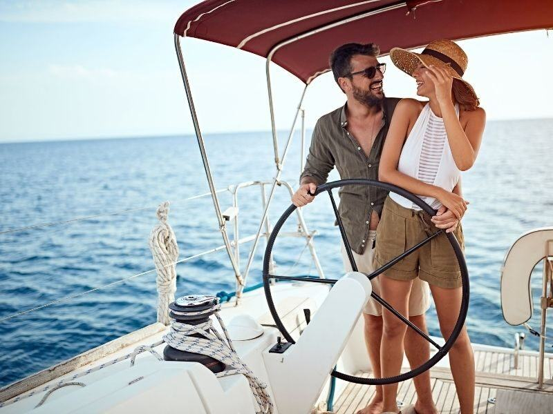 A man and woman at the helm on a sailing vessel