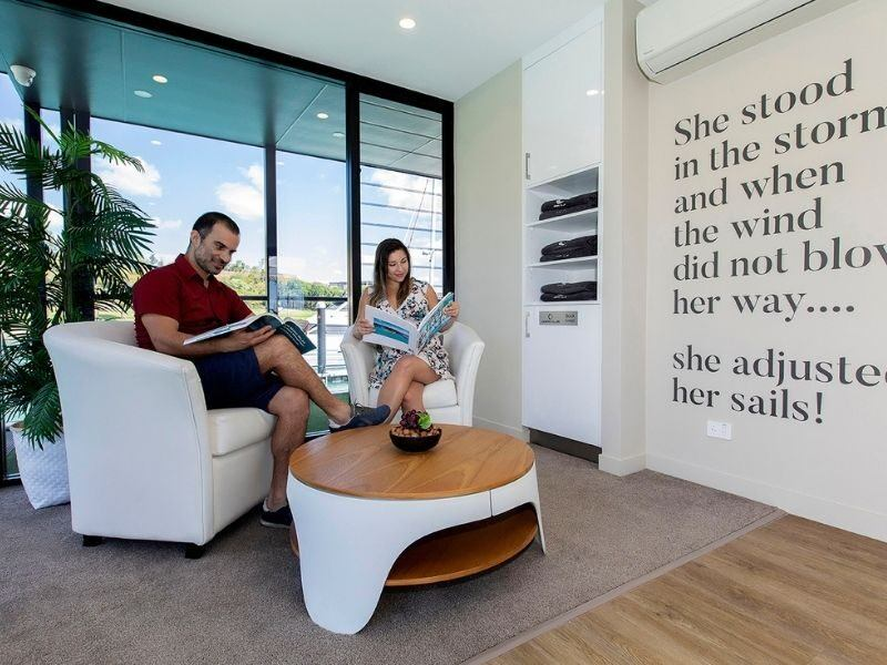 A man and woman sitting in relaxing chairs reading magazines at the Ocean Club, Coral Sea Marina