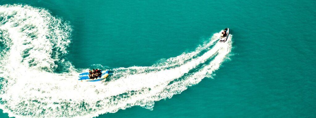 A banana boat with a group of people on it being pulled through the water by a Jet Ski