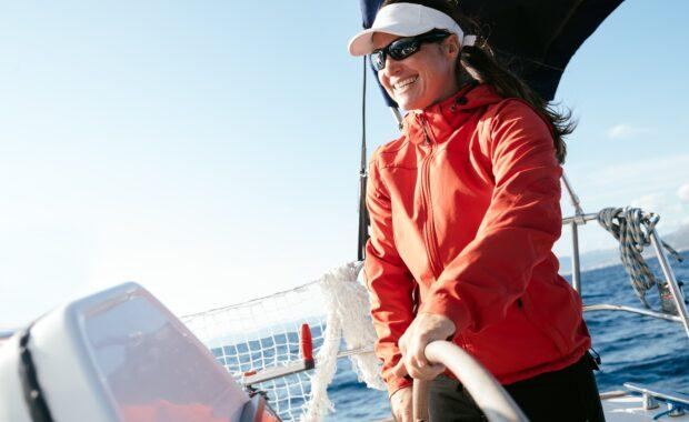 A woman at the helm of a sailing vessel