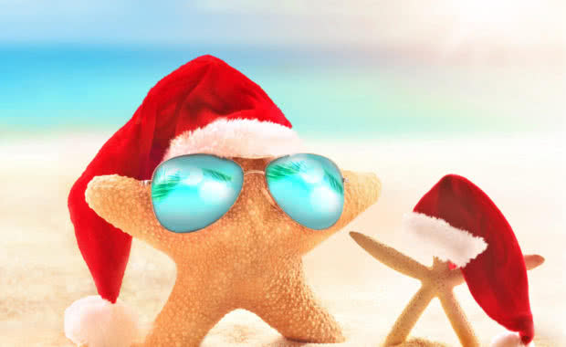 Starfish in sunglasses on summer beach and santa hat. Merry Christmas